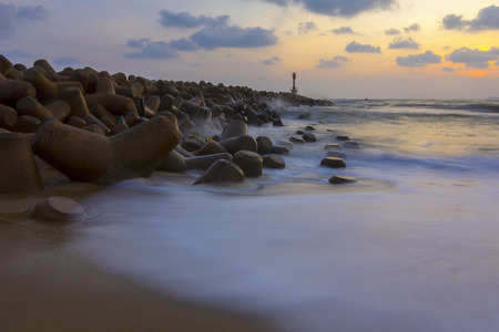 rough sea: view of the morning on the beach and the lighthouse, the water rough sea