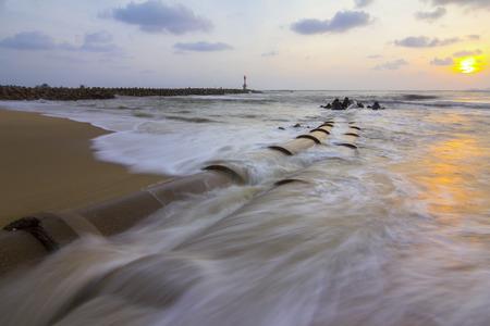 mare agitato: vista della mattina sulla spiaggia e il faro, il mare mosso acqua. l'esposizione a lungo
