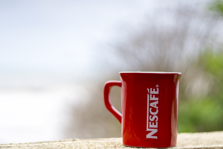 nestle: TERENGGANU, MALAYSIA - 09022016 : Outdoor shot of a red Nescafe cup, background blur.