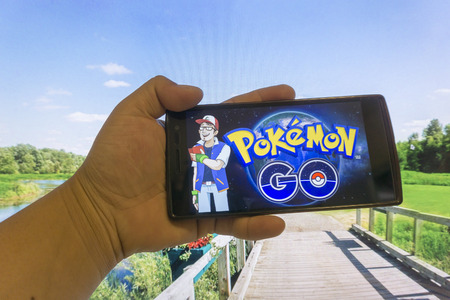 KUALA LUMPUR, MALAYSIA - 16072016: Oppo Find7a held in one hand showing its screen with Pokemon Go application. A free-to-play augmented reality mobile game developed by Niantic for iOS and Android devices. Editorial