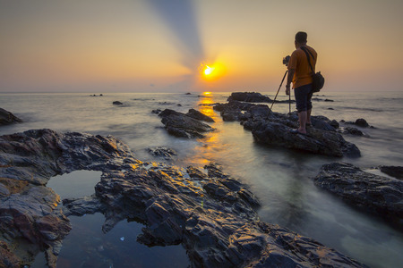 capturing: TERENGGANU - 04072016 : a photographer was capturing the sunrise on the beach were filled with stones