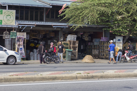 civilians: JERLUN KEDAH, MALAYSIA - 19032016: civilians in front of a pet store roadside in the morning.