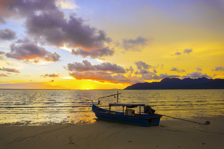 sunset on the beach and saw a fishing boat on the coast Stock Photo