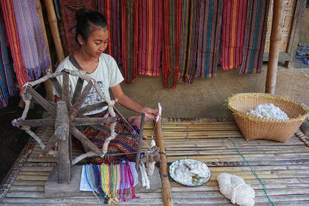 LOMBOK, INDONESIA : 16092016 - Sasak lady traditionally makes yarn with a spindle wheel at traditional Sasak village, Desa Sasak Sade, Lombok Indonesia. Editorial