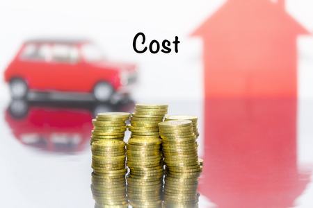 cost saving: Saving money concept and write the word cost. Coins stacks grow the business. Background and toy car and home are blurred. Stock Photo
