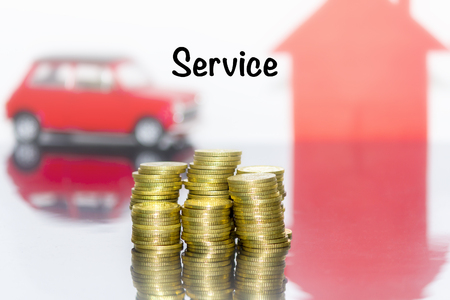 Saving money concept and write the word service. Coins stacks grow the business. Background and toy car and home are blurred.