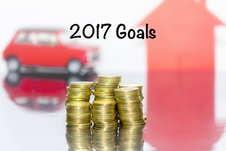 Saving money concept and write the word 2017 goals. Coins stacks grow the business. Background and toy car and home are blurred. Stock Photo