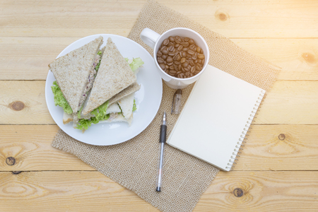 note book, coffee beans and sandwich on the table Stock Photo