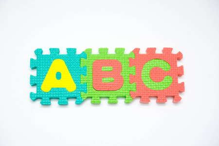 Colorful foam puzzle with word on a white background.
