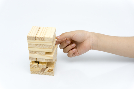 Hand of kid playing a blocks wood tower game of architectural project Stock Photo