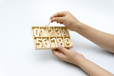 The hand of the child holds the number to be arranged Stock Photo