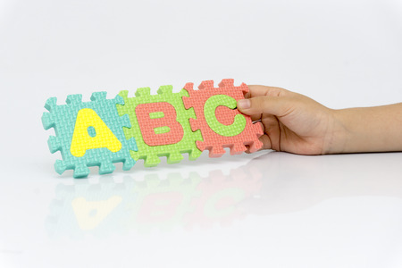 childrens hands hold abc puzzle