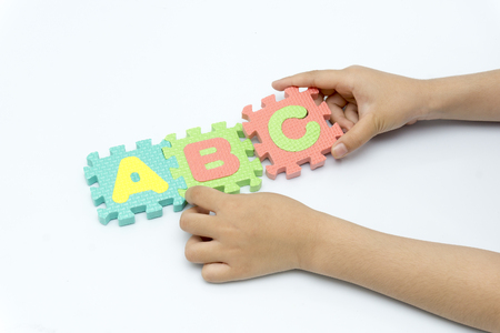 children's hands hold abc puzzle