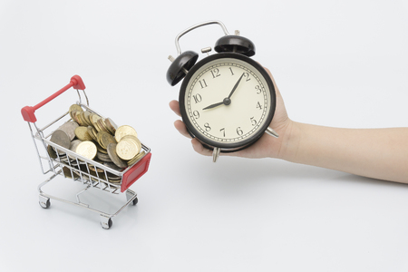 childrens hands hold bell clocks and coin trolley