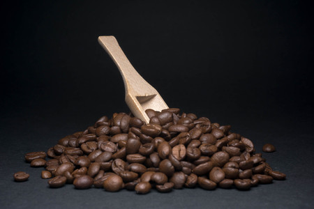 coffee beans and wooden spoon with low light