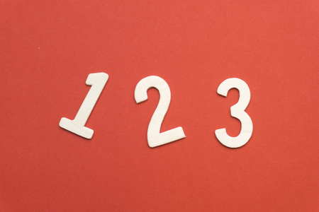 number 1 2 3 of wood on red paper