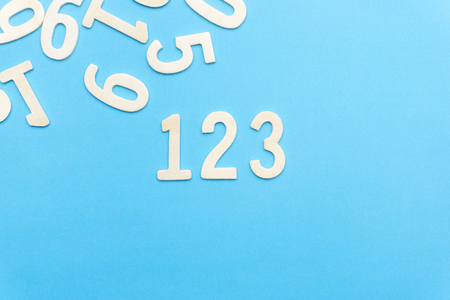 number 1 2 3 of wood on blue paper