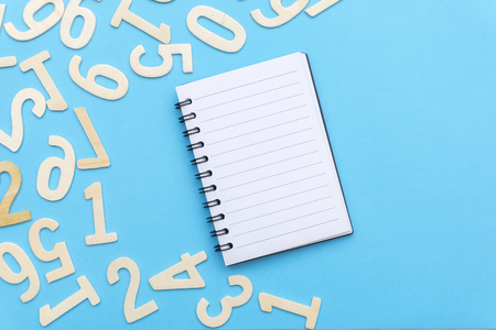 note book and scattered numbers on blue paper