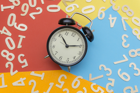 a black bell clock in the middle of a colorful paper and a scattered number