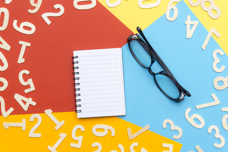 notebooks and glasses in the center of colorful paper and scattered numbers