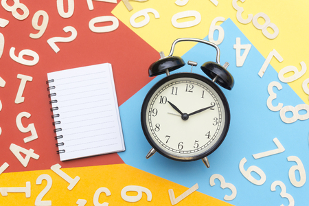 notebooks and alarm clocks in the center of colorful paper and scattered numbers Stock Photo