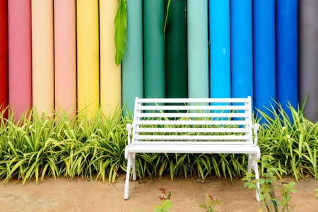 White iron bench and multicolor concrete fence in the garden.