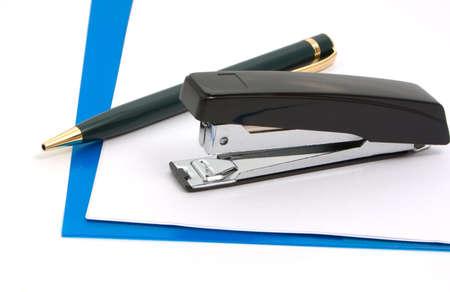 Stapler, pen and blue folder on white background