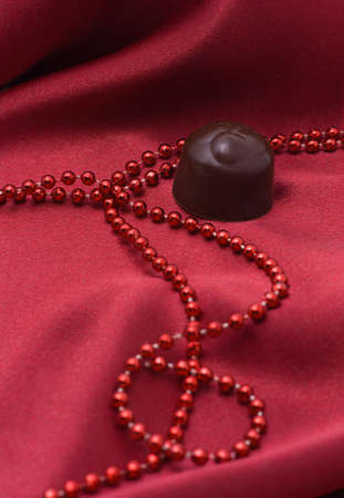 Chocolate and red beads on a satiny drapery   photo