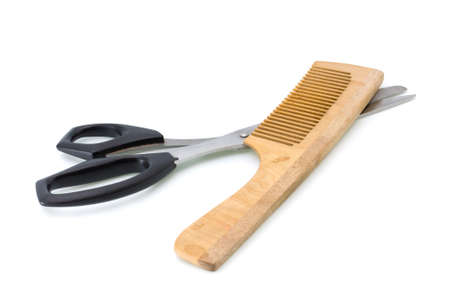 Some wooden hairbrush and scissors on a white background