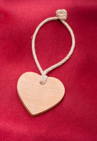 Wooden heart on a red satiny drapery - Souvenir by day of sacred Valentine  (Valentin-day)