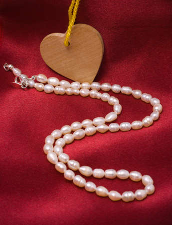 White pearls and wooden heart on a red satin drapery