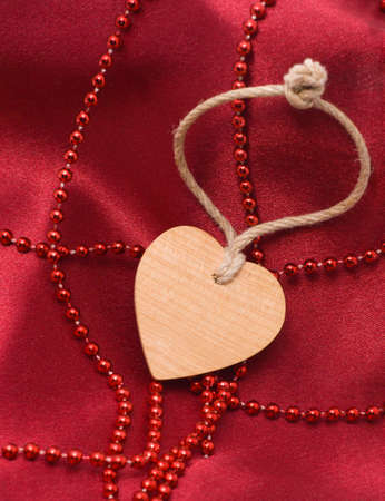 Wooden heart and red beads on a satiny drapery - Souvenir by day of sacred Valentine  (Valentin-day) Stock Photo