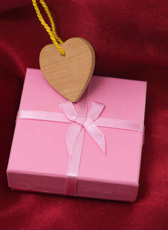 Wooden heart and gift on a satiny drapery - Souvenir by day of sacred Valentine  (Valentin-day)
