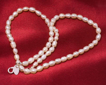 White pearls on a red satin drapery - In the form of heart