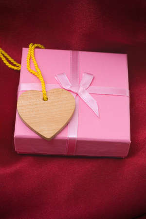 Wooden heart and gift on a satiny drapery - Souvenir by day of sacred Valentine (Valentin-day) Stock Photo