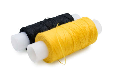 Two coils of yellow and black threads for sewing on a white background
