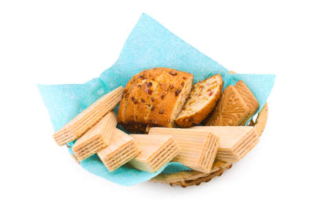 Wafers, a fruitcake and cookies in a wattled basket on a white background