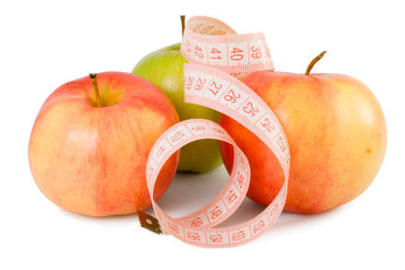 Pink measuring tape and three apples on a white background