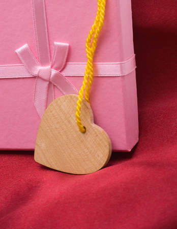 Wooden heart and gift on a satiny drapery - Souvenir by day of sacred Valentine(Valentin-day) Stock Photo