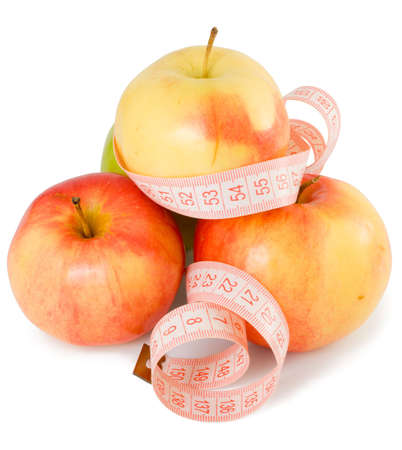 Pink measuring tape and some apples on a white background