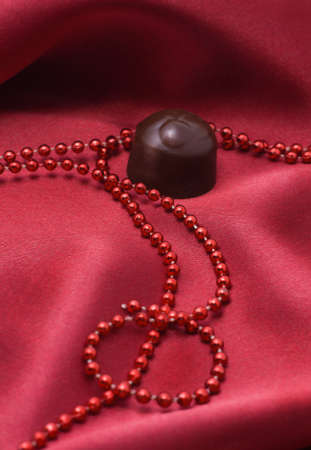 Chocolate and red beads on a satiny drapery Stock Photo