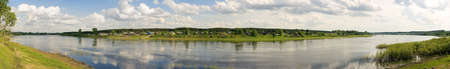 Panorama of a summer landscape with the river,wood and village.River - Suhona - big river in Vologda region (Russia)