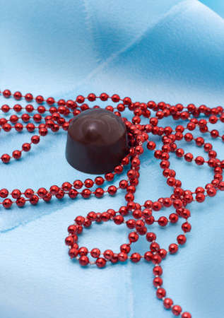 Chocolate and red beads on a blue satiny drapery