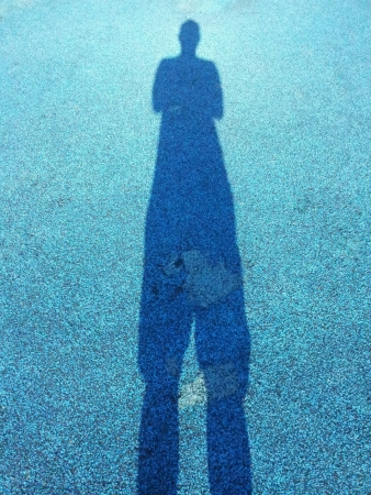 self portrait of man producing a tall shadow Stock Photo
