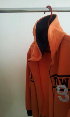 Orange color jacket sweater hanging inside room