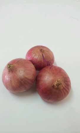 Three fresh red onions on white background