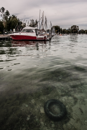 alpes: Sunken tyre in the the Annecy Lake and anchored yachts