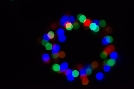 Christmas garland of garland glowing with different colors, green, red, blue, in the dark, blurry lights