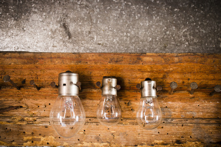 woodcraft: small, medium and large bulbs on the nails on the old wooden stand