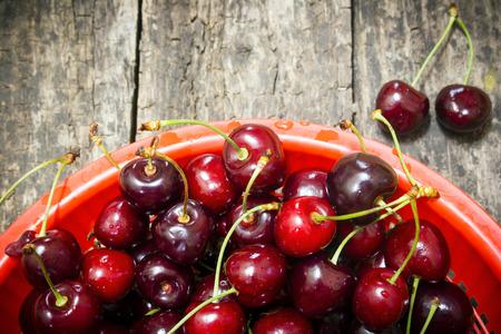 secchio rosso perlustrato ciliegie rurale su un tavolo di legno